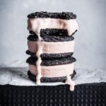 Stack of three chocolate blood orange ice cream sandwiches with bite taken out and ice cream drip