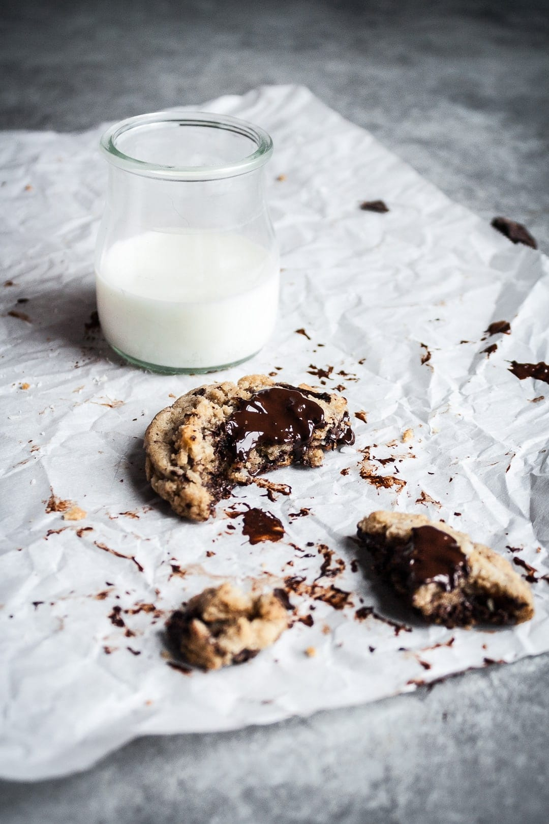 A partially eaten coconut chocolate chip cookie on parchment paper with a glass of milk nearby