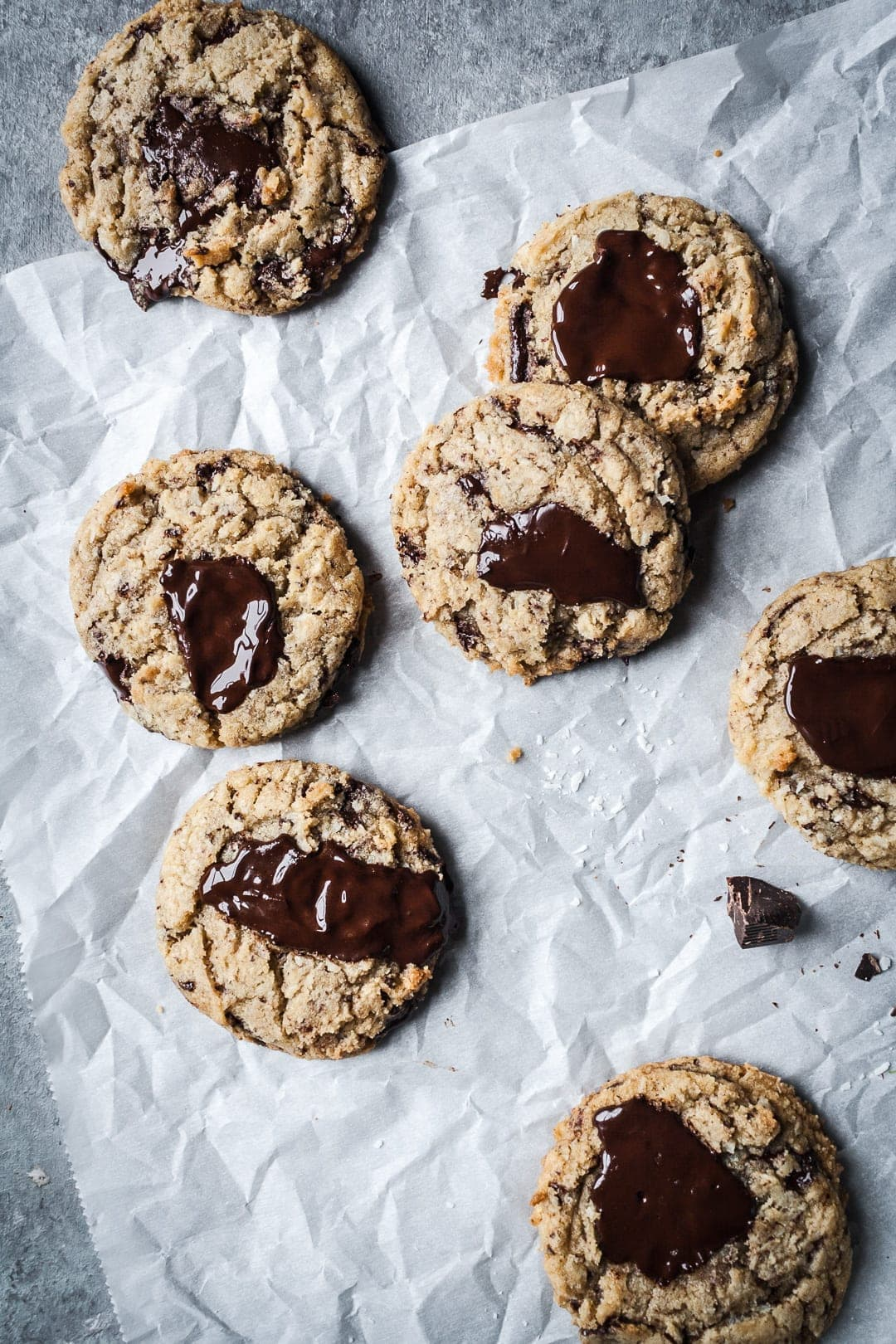 Top view of freshly baked coconut chocolate chip cookies with melted pools of chocolate resting on parchment paper
