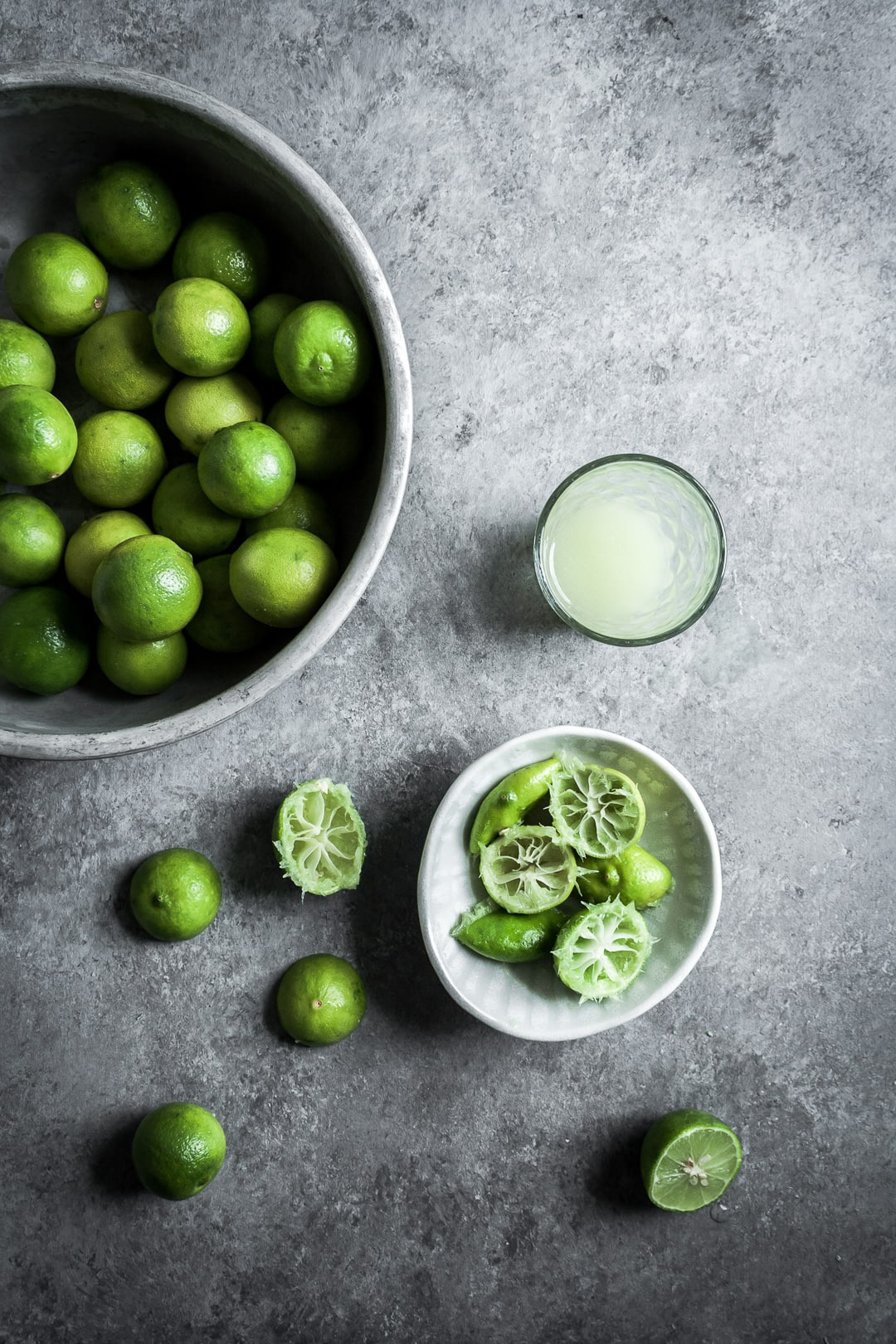 Key limes in a bowl, some cut in half and squeezed, with a glass of key lime juice on a grey background