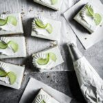 Top view of sliced cheesecake bars on parchment paper squares on a grey background with a piping bag of whipped cream nearby