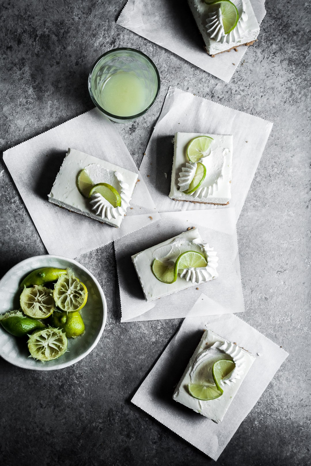 Key Lime cheesecake bar slices with piped whipped cream and lime twists on squares of parchment paper on a grey background
