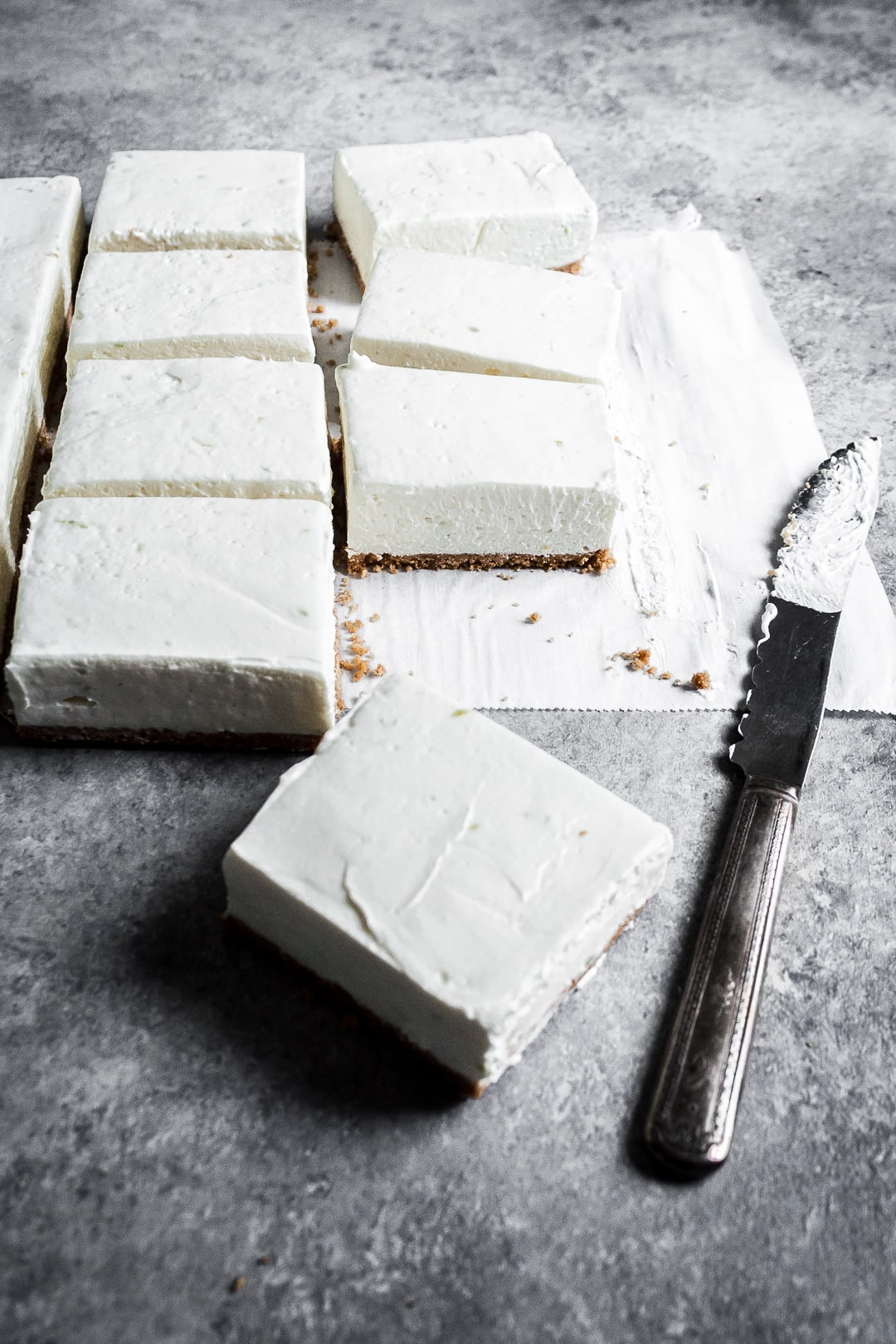 45 degree angle view of sliced cheesecake bars on parchment paper squares on a grey background with a vintage knife nearby
