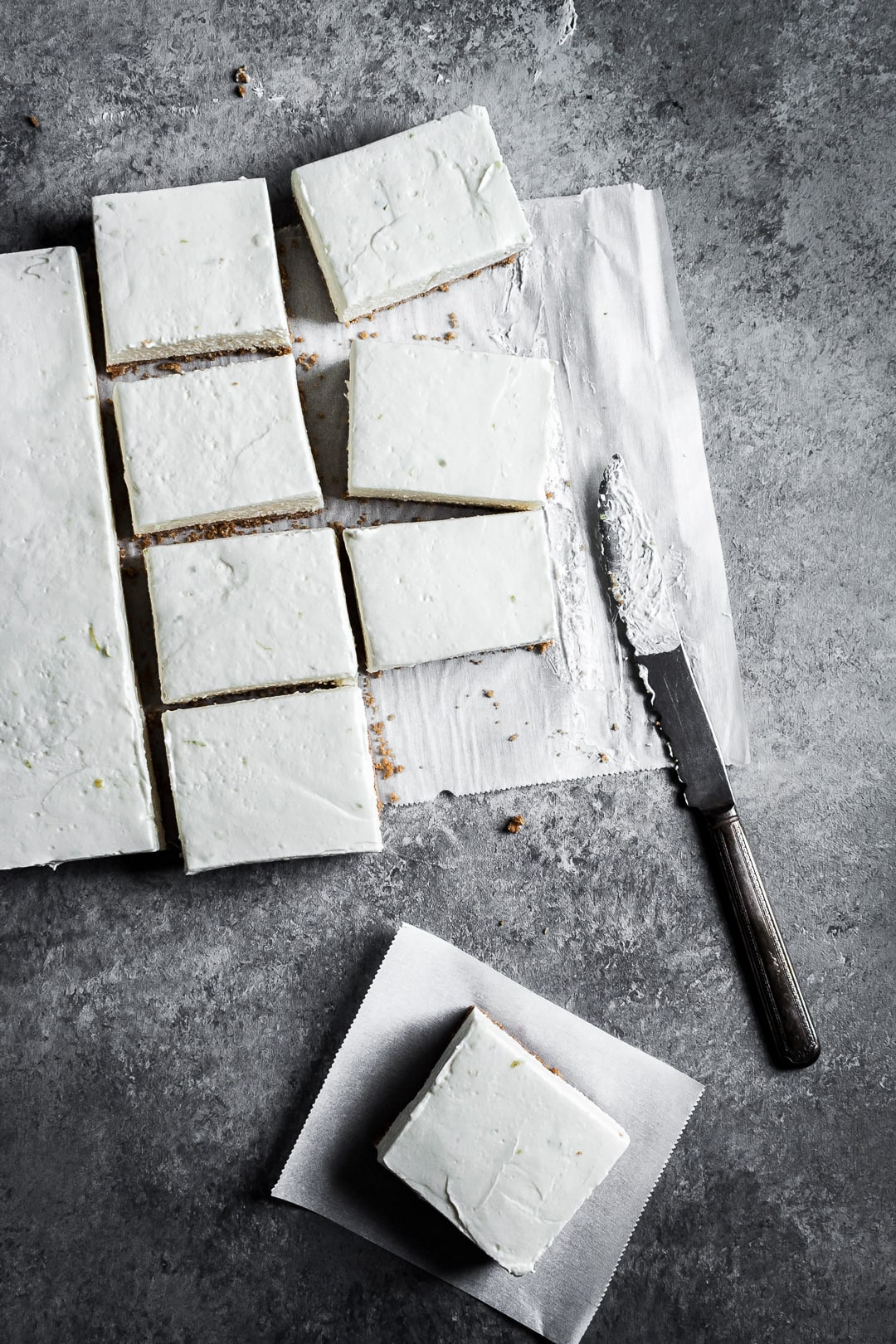 Sliced cheesecake bars on parchment paper squares on a grey background with a vintage knife nearby