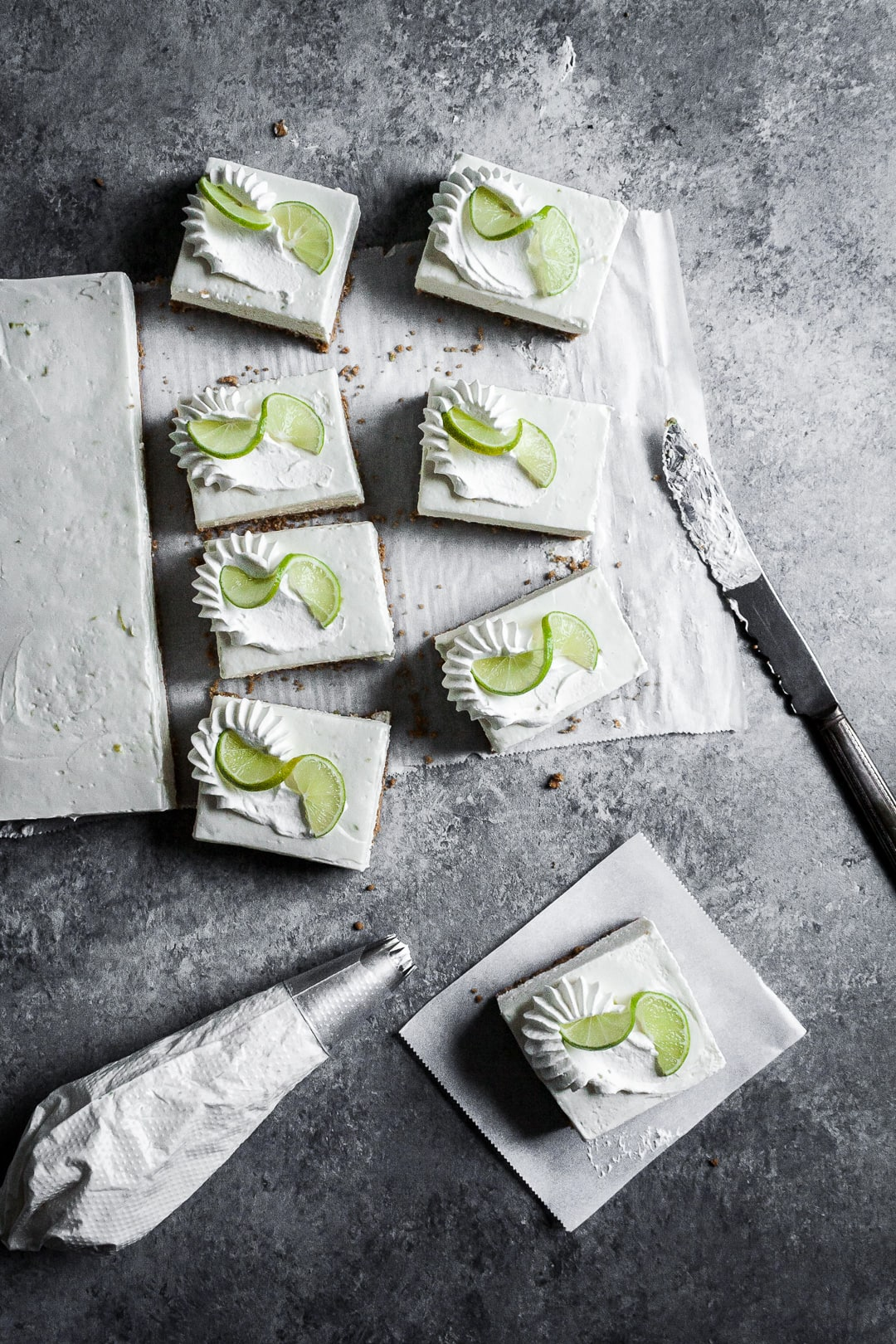 Five sliced cheesecake bars on parchment paper squares on a grey background with a piping bag of whipped cream and vintage knife nearby
