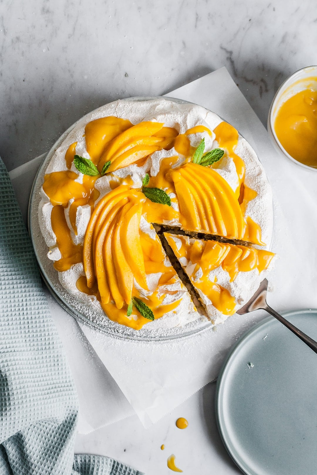 Meringue cake with mangoes on top with a slice being lifted out to put on a plate