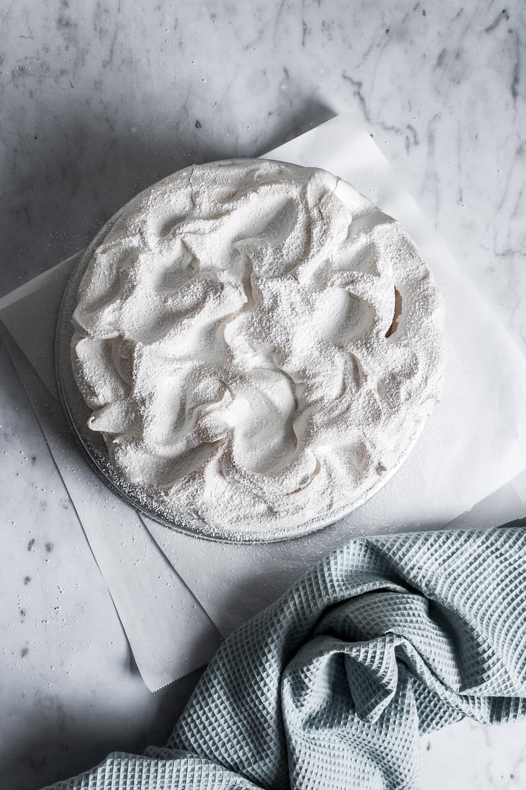 Top view of baked meringue covering a layer cake - on a marble background with parchment paper underneath