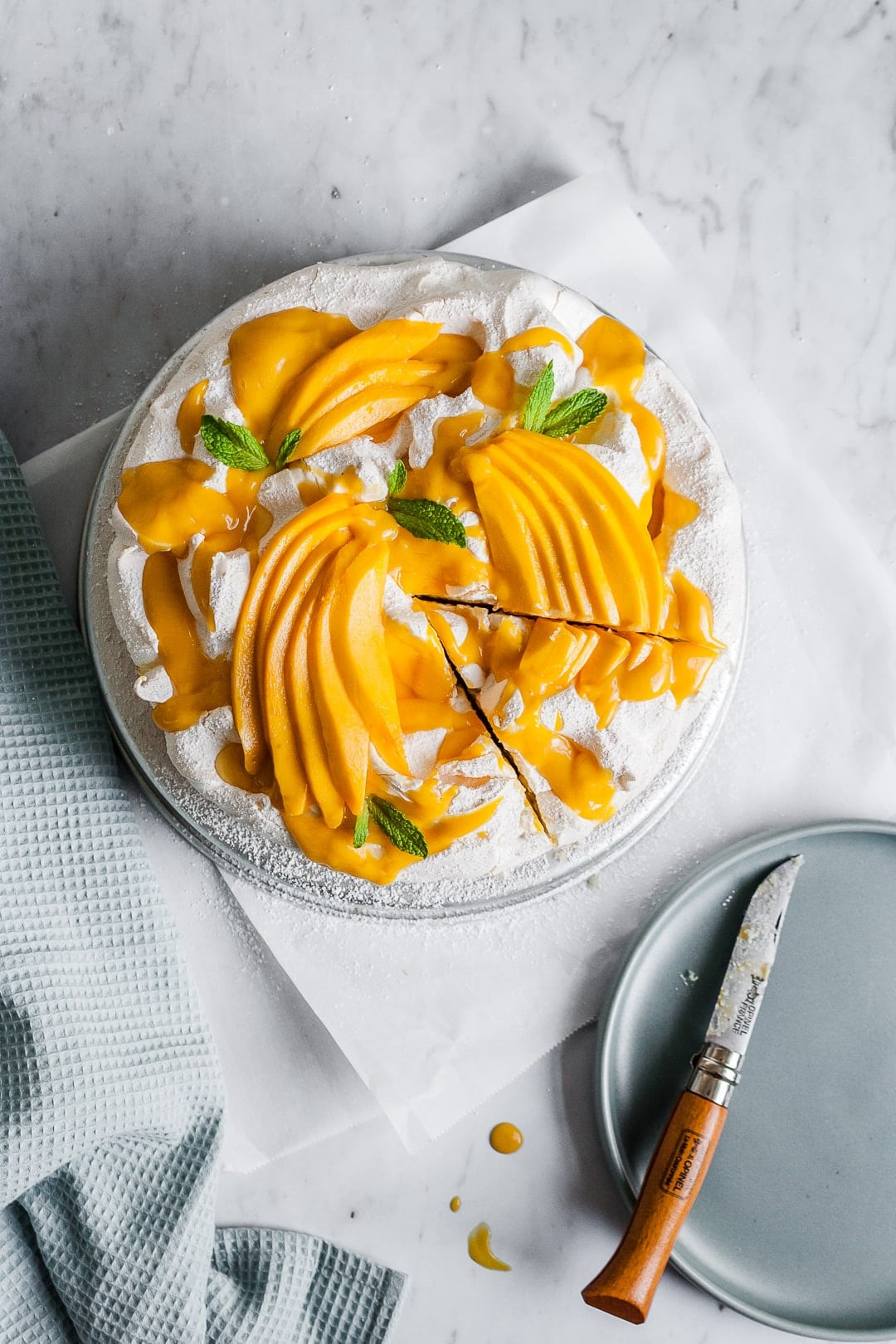 Meringue cake with mangoes on top with slice cut out of it and knife resting on plate nearby