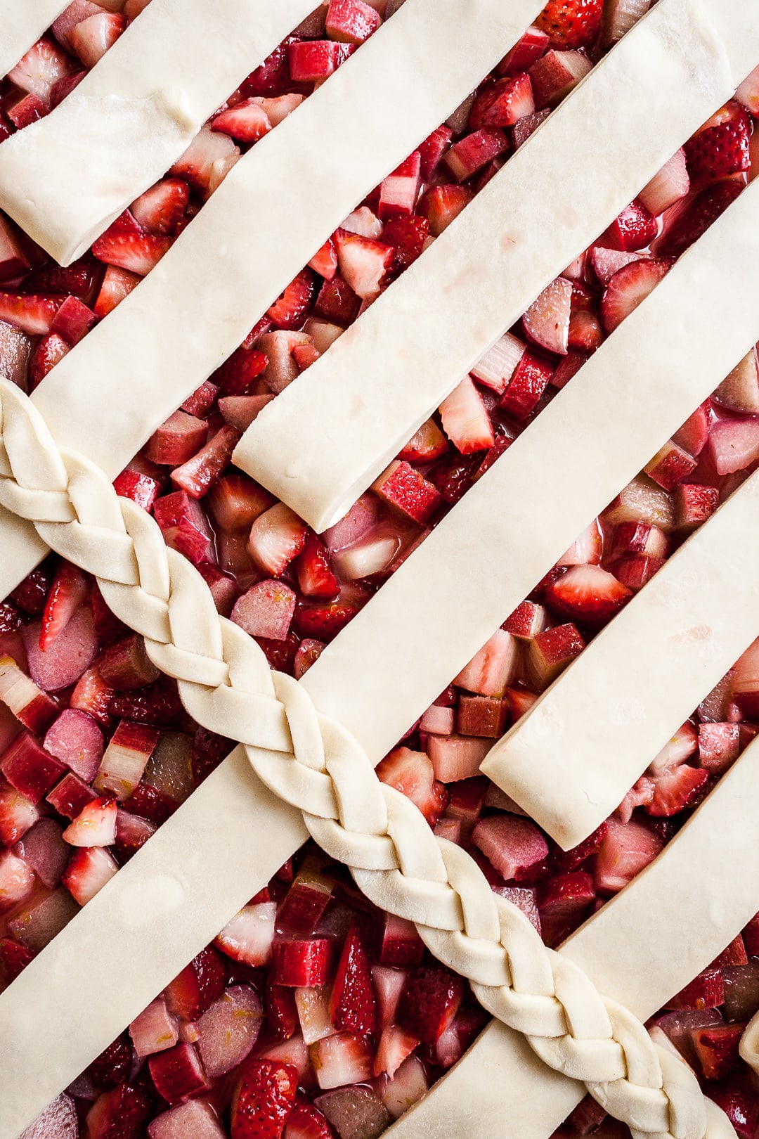 Close up of strawberry rhubarb pie filling with lattice dough strips and braid angled on top