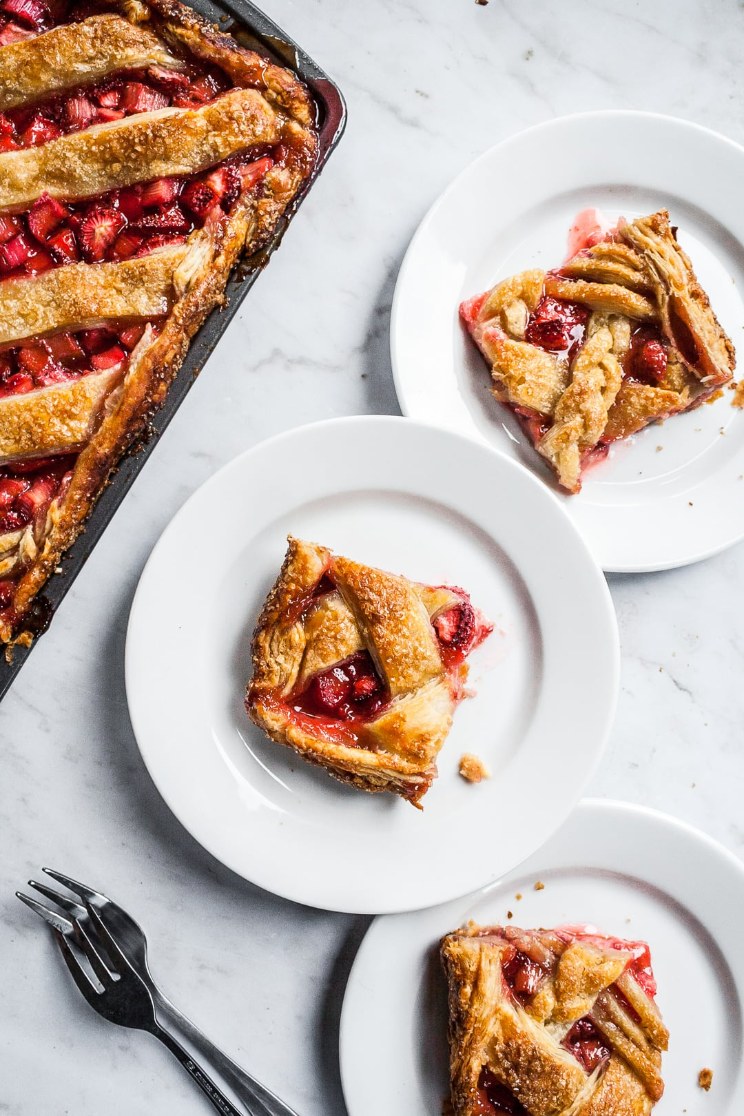 Slices of slab pie on white plates next to a sheet pan of slab pie