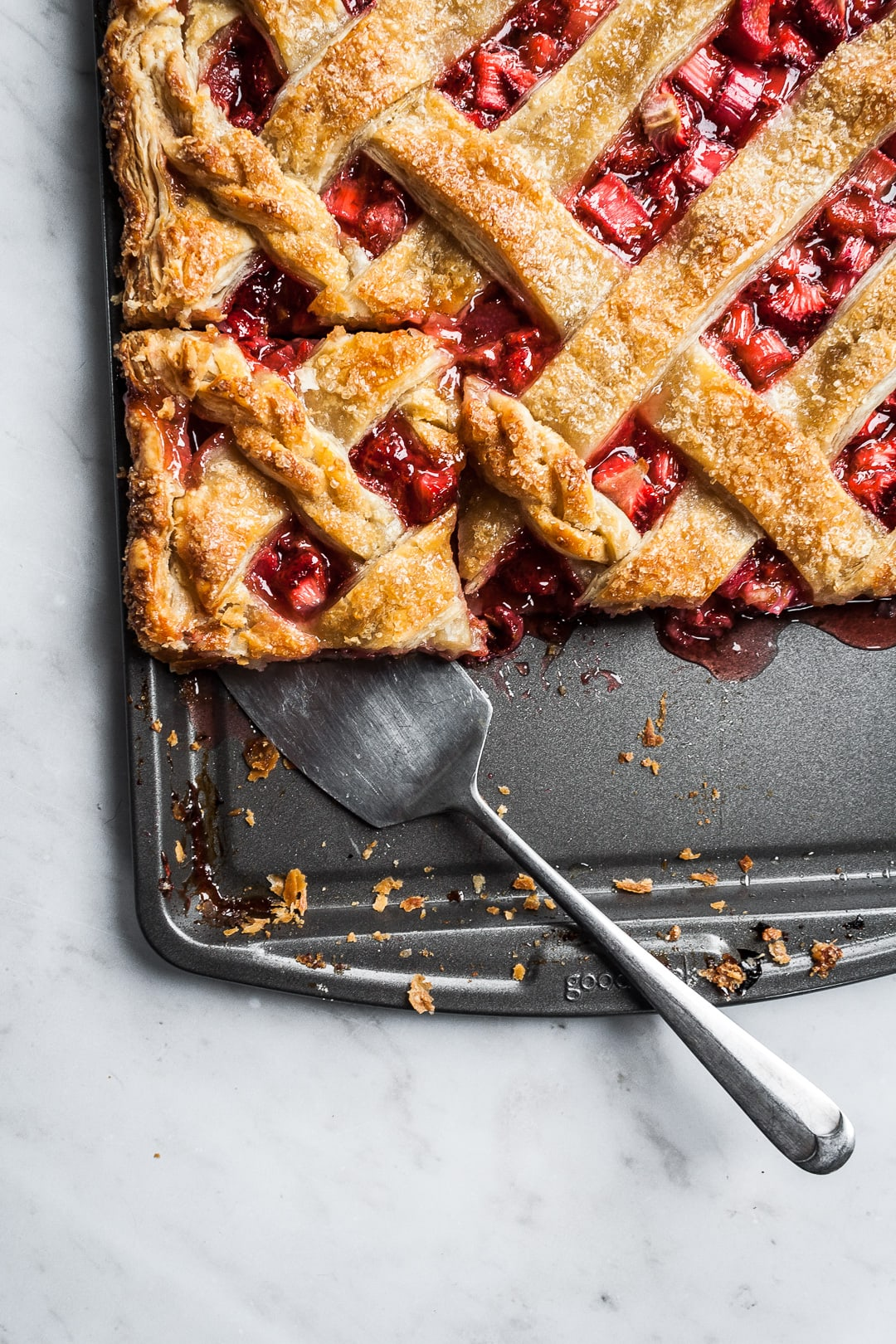 Baked strawberry rhubarb slab pie with a piece cut and being lifted by a serving utensil