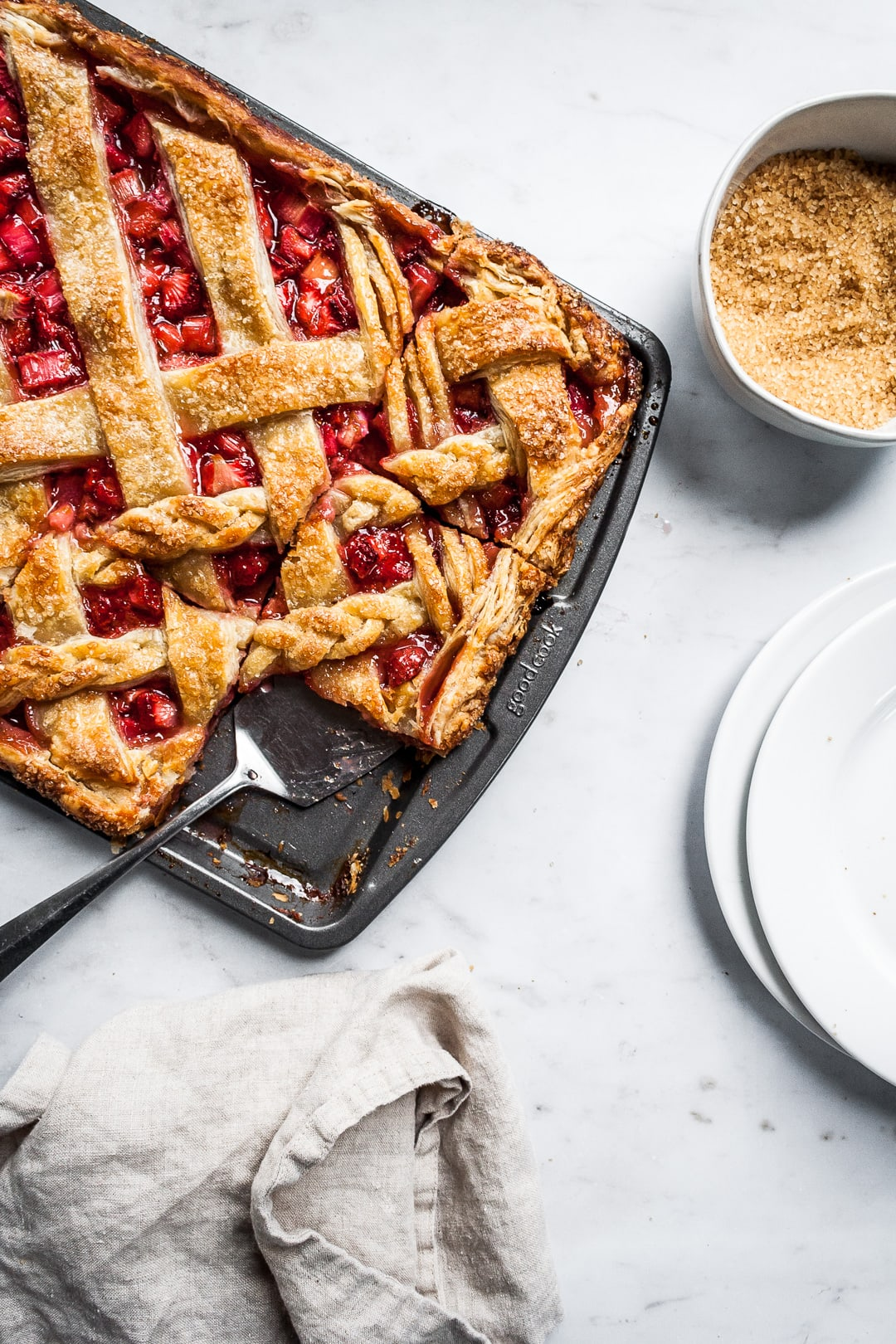 Baked strawberry rhubarb slab pie in a sheet pan with several cut slices and a serving utensil on a marble background