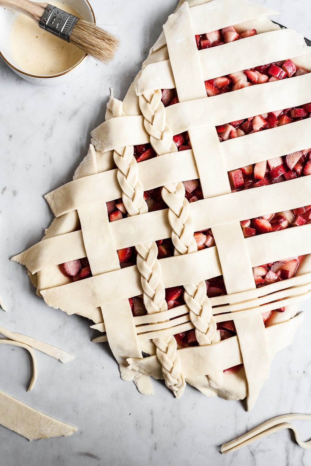 Top view of unbaked strawberry rhubarb slab pie with angled woven lattice crust with braids on a white background