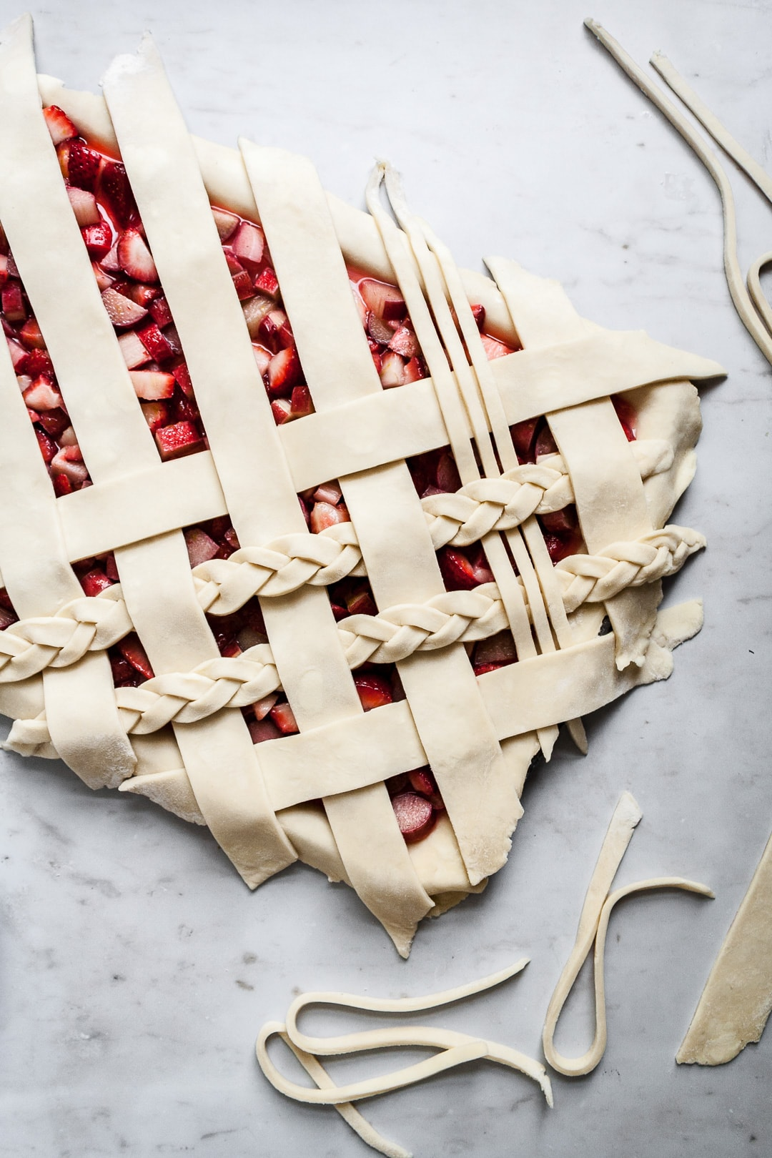 Top view of unbaked strawberry rhubarb slab pie with angled woven lattice crust with braids on a marble background with dough scraps nearby