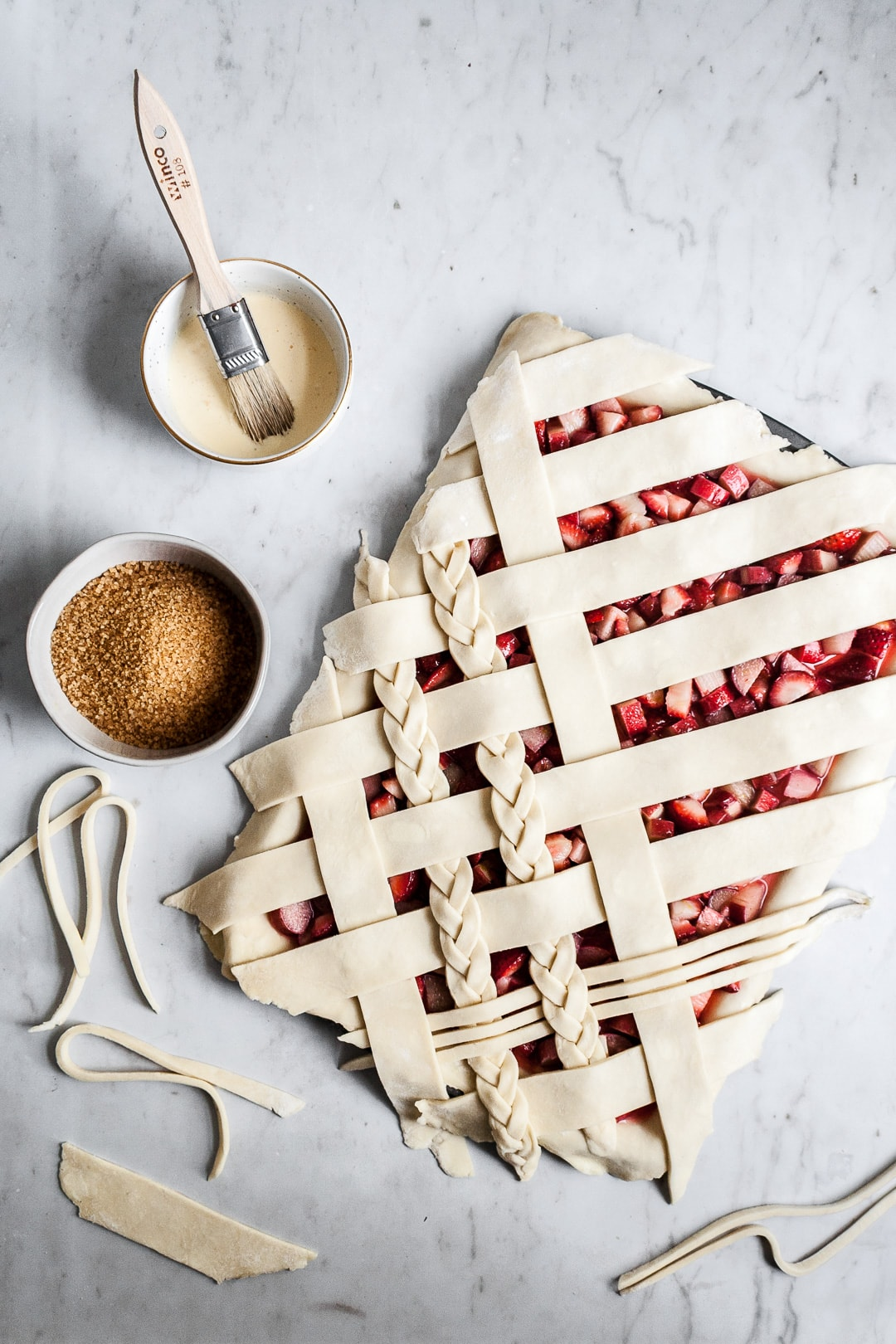 Top view of unbaked strawberry rhubarb slab pie with angled woven lattice crust with braids on a marble background and bowls of egg wash and coarse sugar nearby