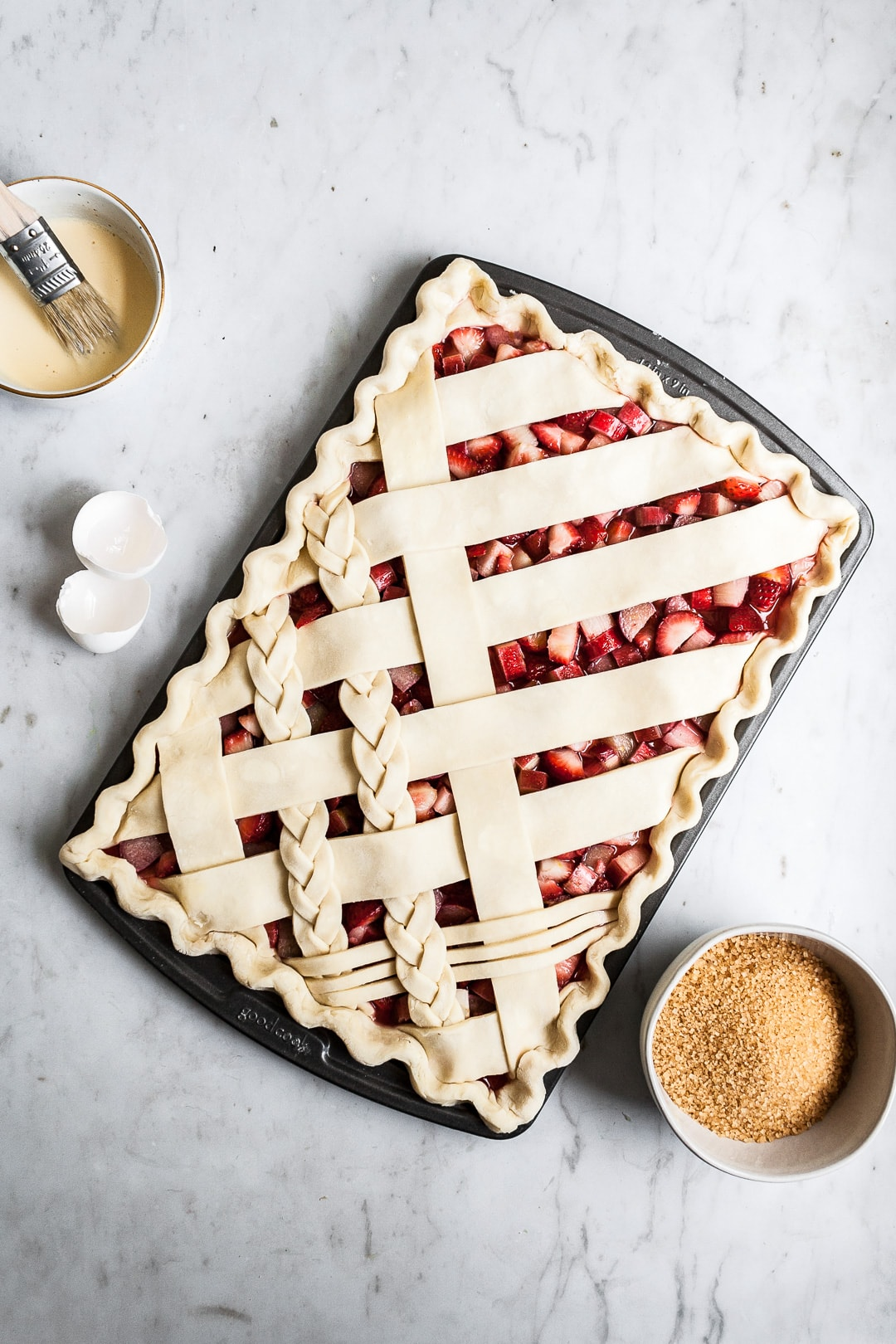 Crimped unbaked lattice slab pie crust in sheet pan on a marble background with bowls of sugar and egg wash nearby