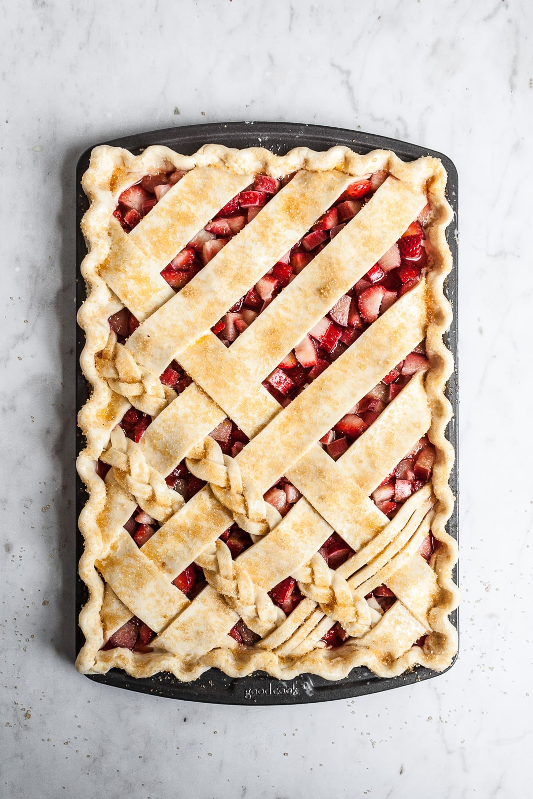 Top view of unbaked crimped lattice slab pie with strawberry rhubarb filling, sprinkled with coarse sugar, on a marble background