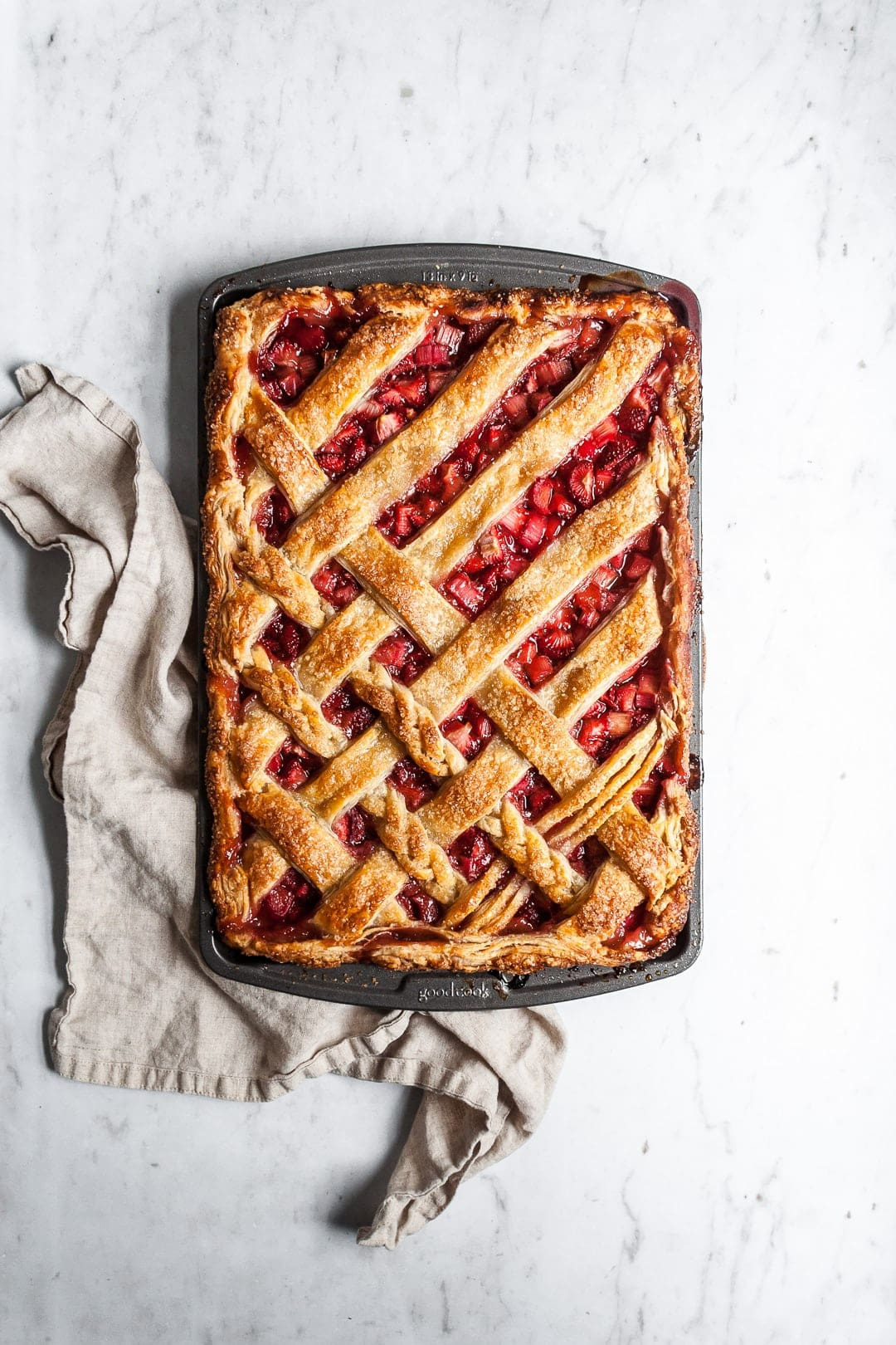 Top view of baked strawberry rhubarb slab pie with natural linen towel underneath pan, resting on a marble background