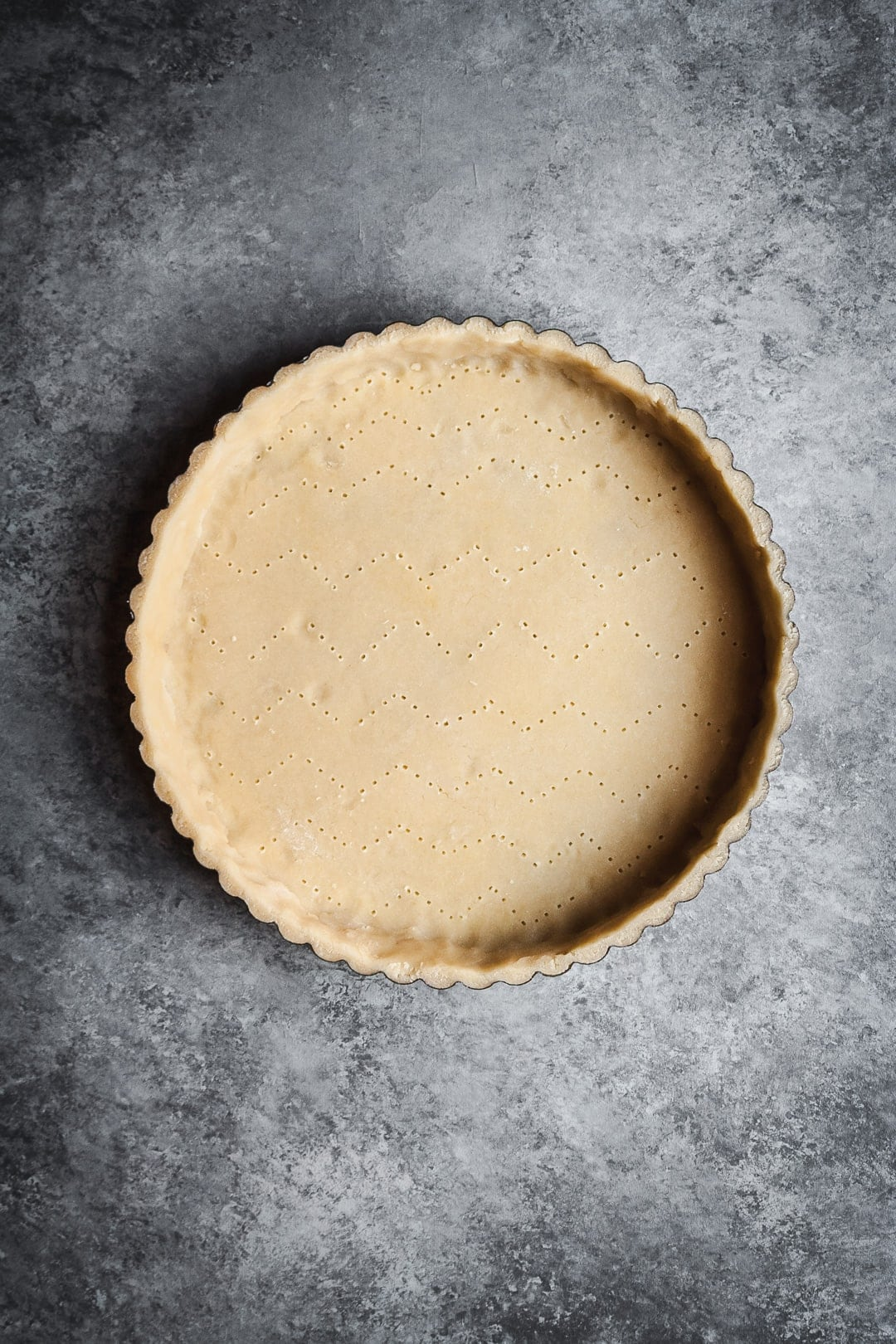 Unbaked tart shell on a grey background