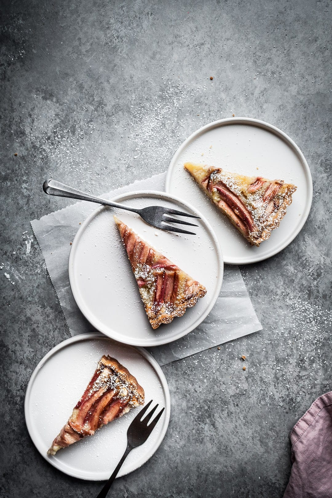 Three white plates with rhubarb tart slices and silver forks on a grey background