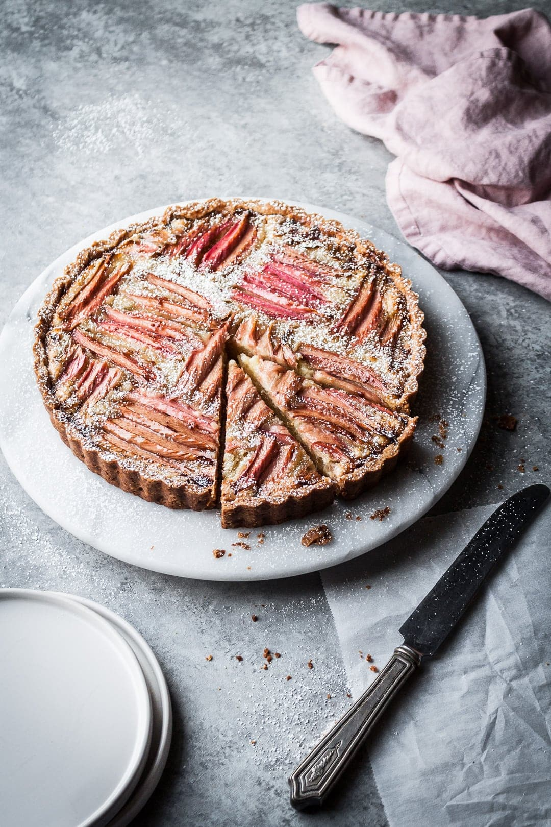 Rhubarb tart from 45 degree view with slices cut and knife on grey background nearby
