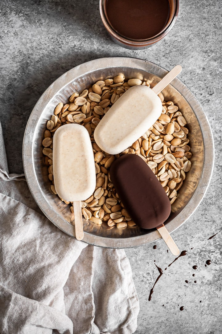 Ice cream bars in a tray filled with peanuts
