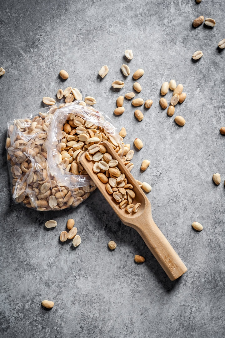 Bag of peanuts strewn on grey surface with a wooden scoop