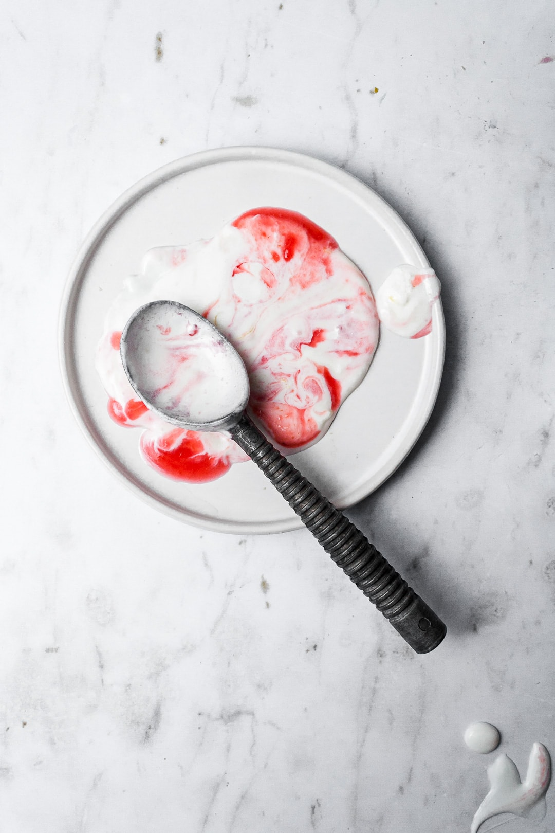 Melted puddle of marbled red and white ice cream on a white plate with a vintage ice cream scoop on top