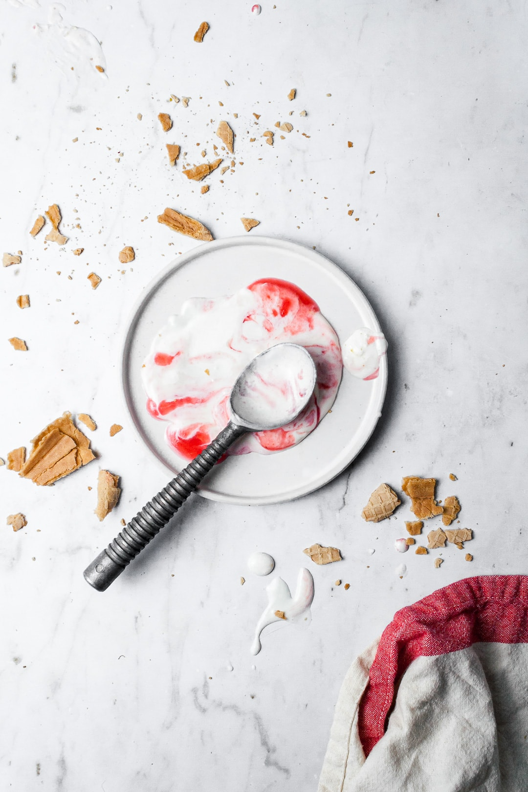 Melted puddle of red and white ice cream on a white plate with crushed sugar cone strewn nearby