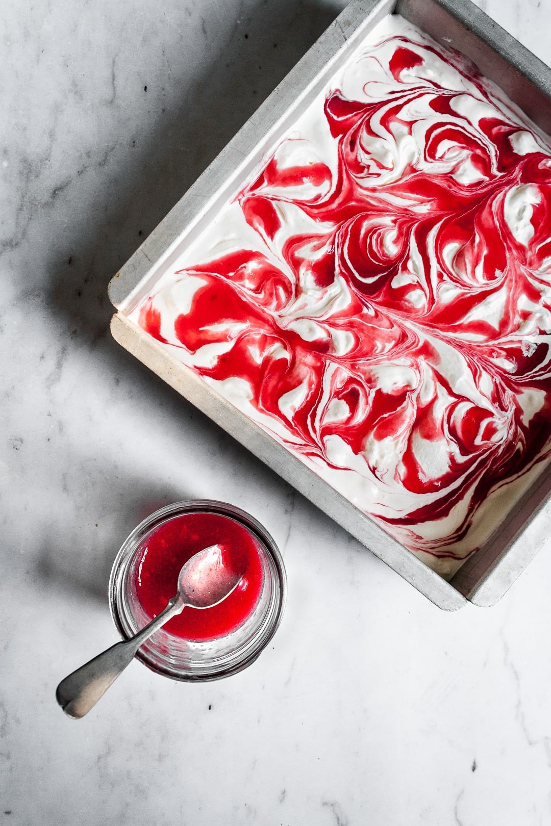 Lemon Mascarpone Ice Cream with Currant Swirl in a square metal pan with a jar of currant sauce and spoon nearby