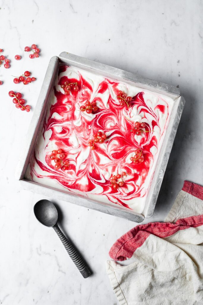 Lemon Mascarpone Ice Cream with Currant Swirl in a square metal pan with loose bunches of currants strewn over the top and nearby