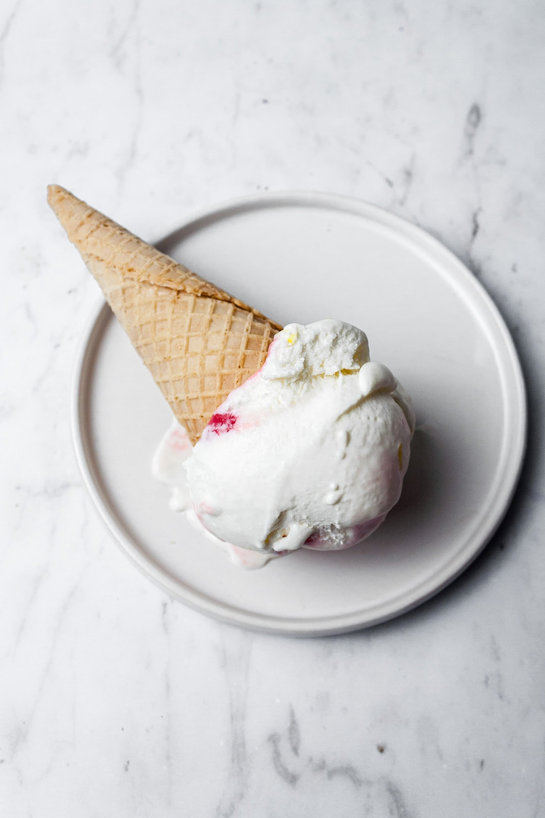 Sugar cone with scoop of ice cream on a white plate and marble background