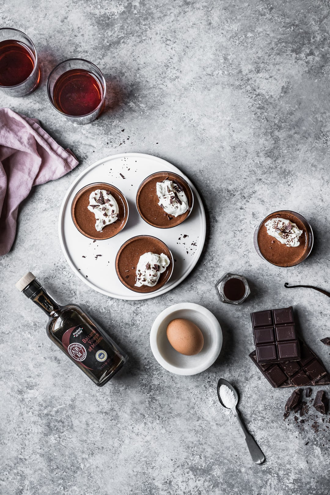 Chocolate pots de creme on a grey background surrounded by the recipe ingredients