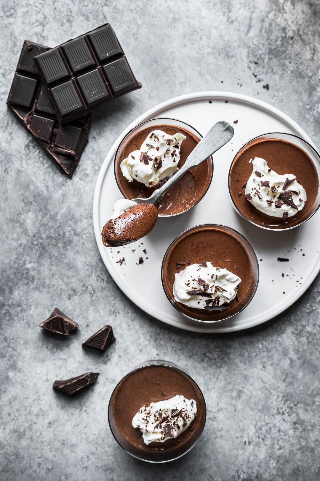 Top view of chocolate pots de creme on a white plate and grey background with chocolate scattered nearby