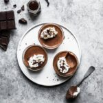 Chocolate pots de creme on a white plate and grey background with ingredients and spoon nearby