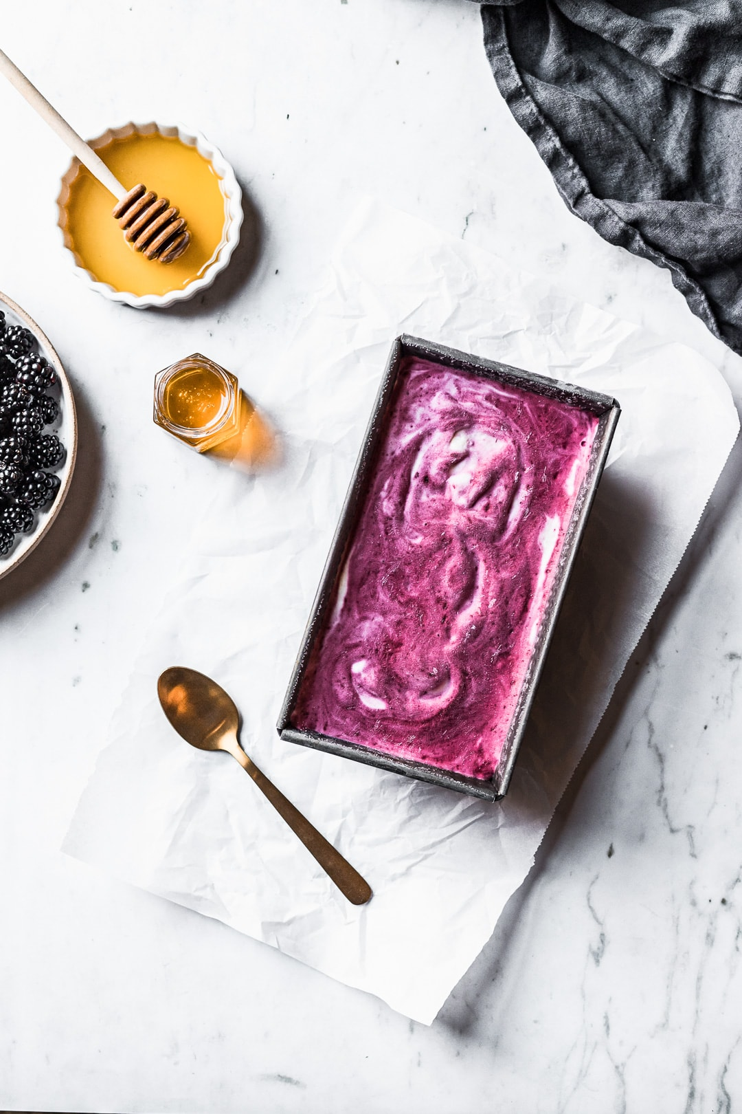 Purple and white swirled ice cream in a container on a marble background with blackberries and honey nearby