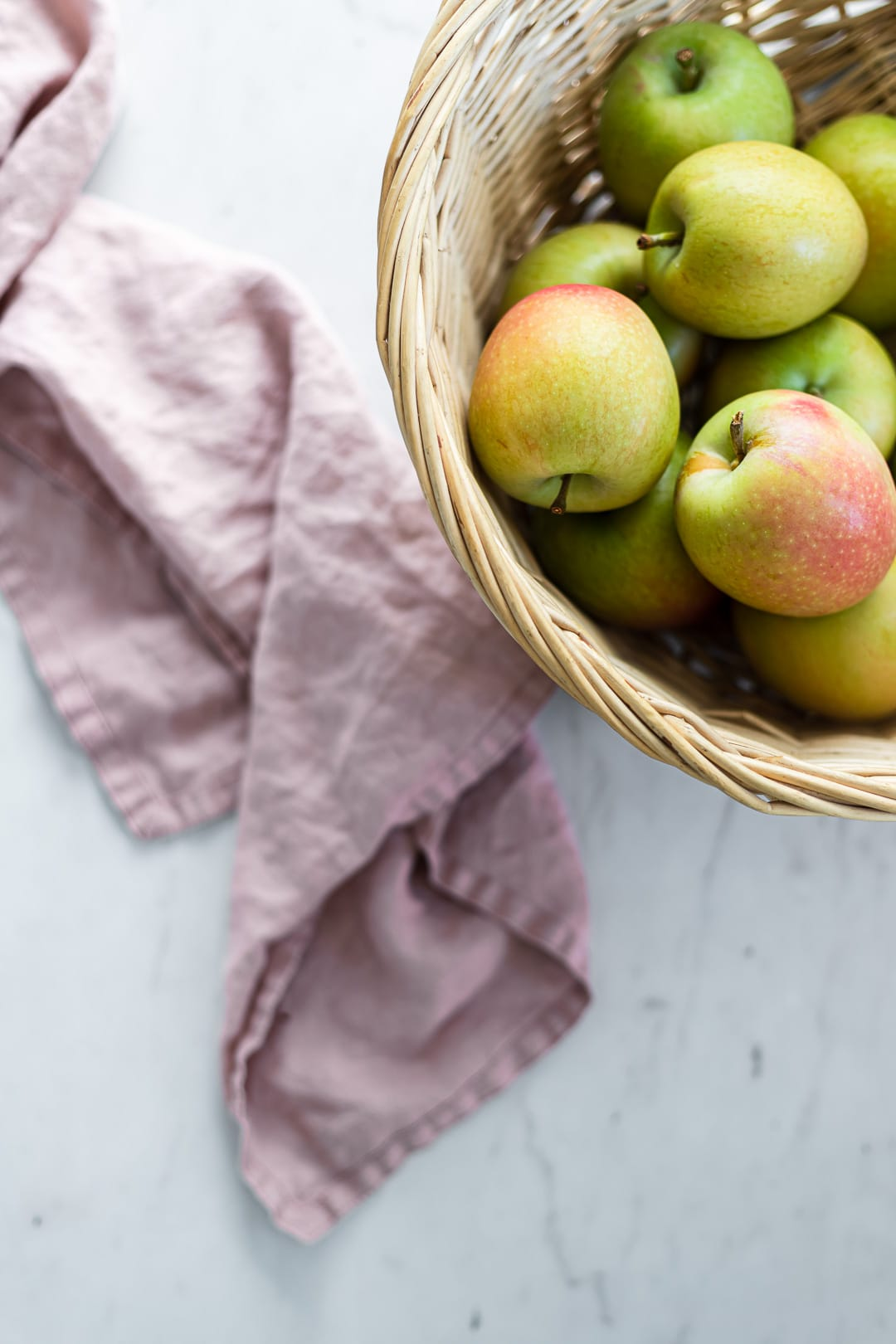 Green apples in a basket on a white marble background with pink linen nearby