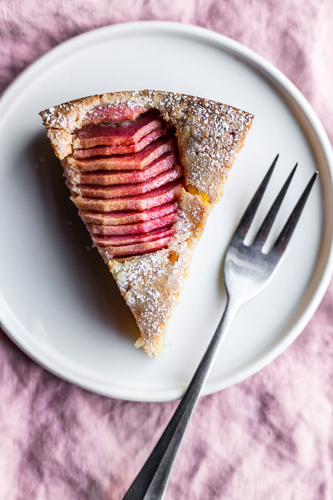 Slice of almond cake with sliced pink apples on a white plate on a pink napkin