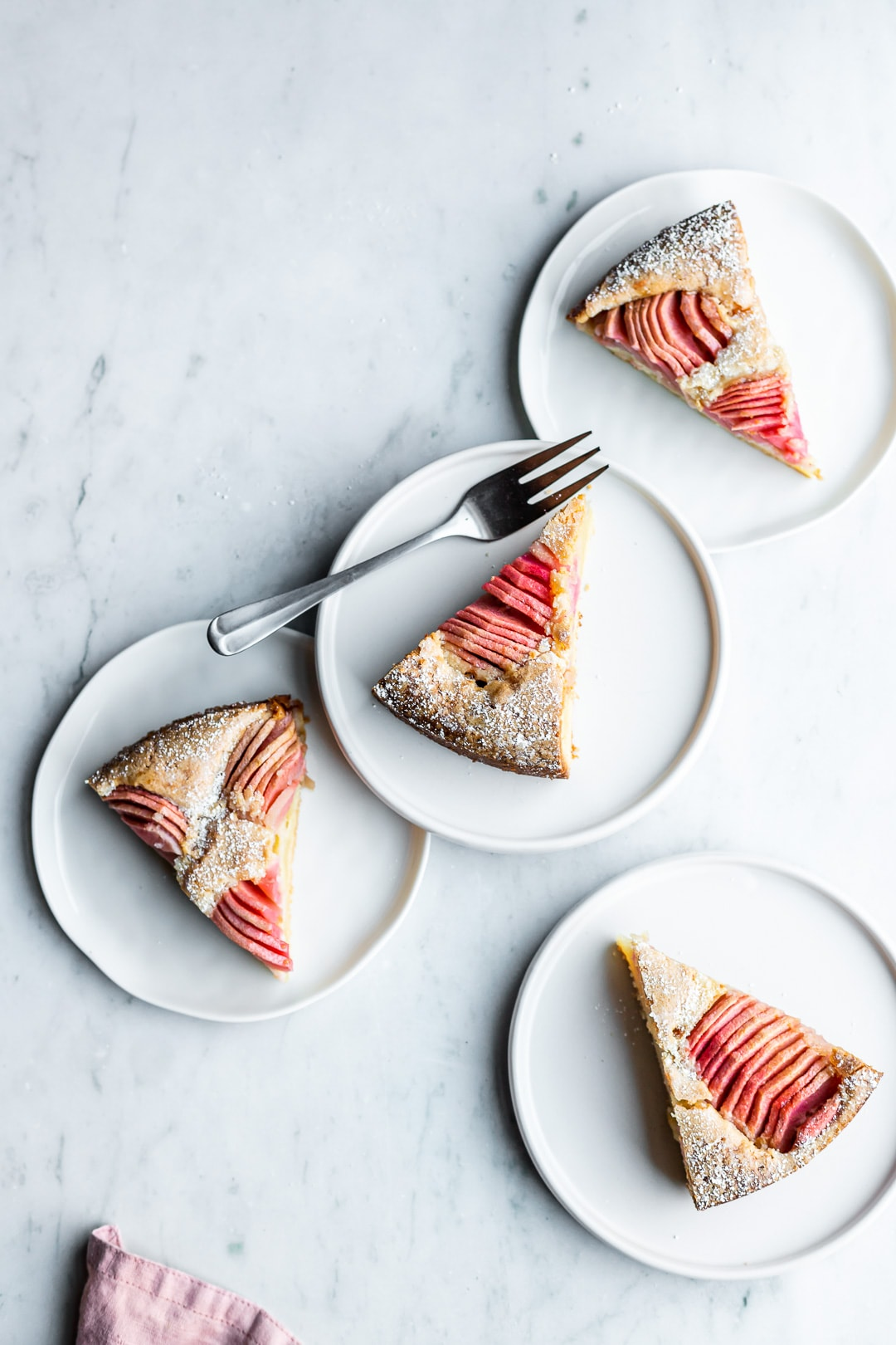 Slices of almond cake with pink apples on four white plates on a marble background