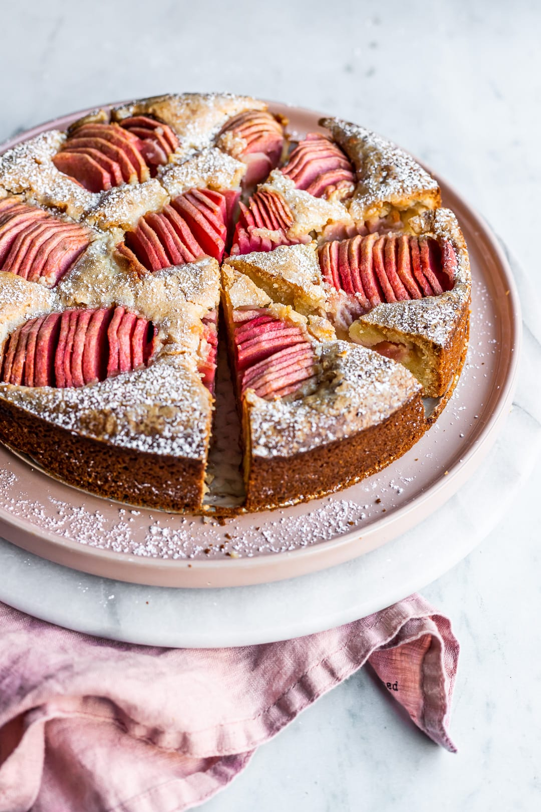 Angled view of sliced almond cake with pink apples on a pink plate and marble background