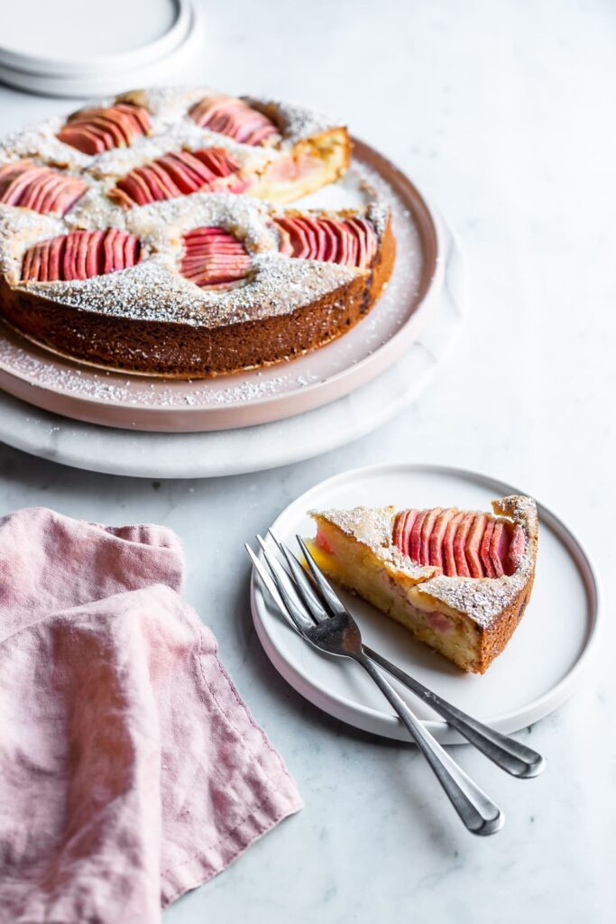 Slice of almond cake with pink apples with rest of cake in background