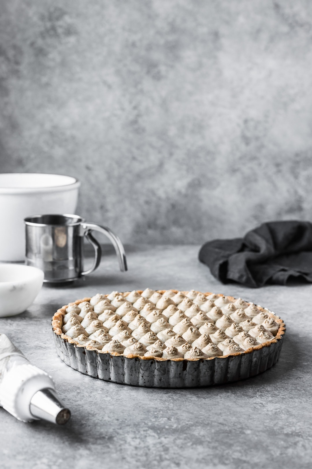 Tart resting on a grey background with bowls and piping bag nearby