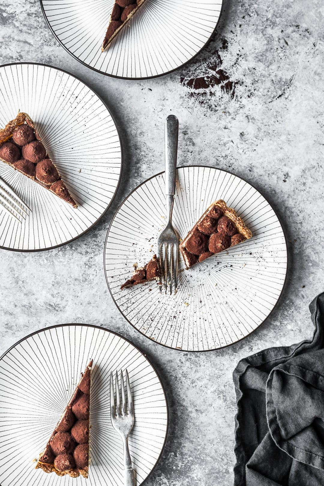 Four plates on a grey background with slices of tart and forks on plates