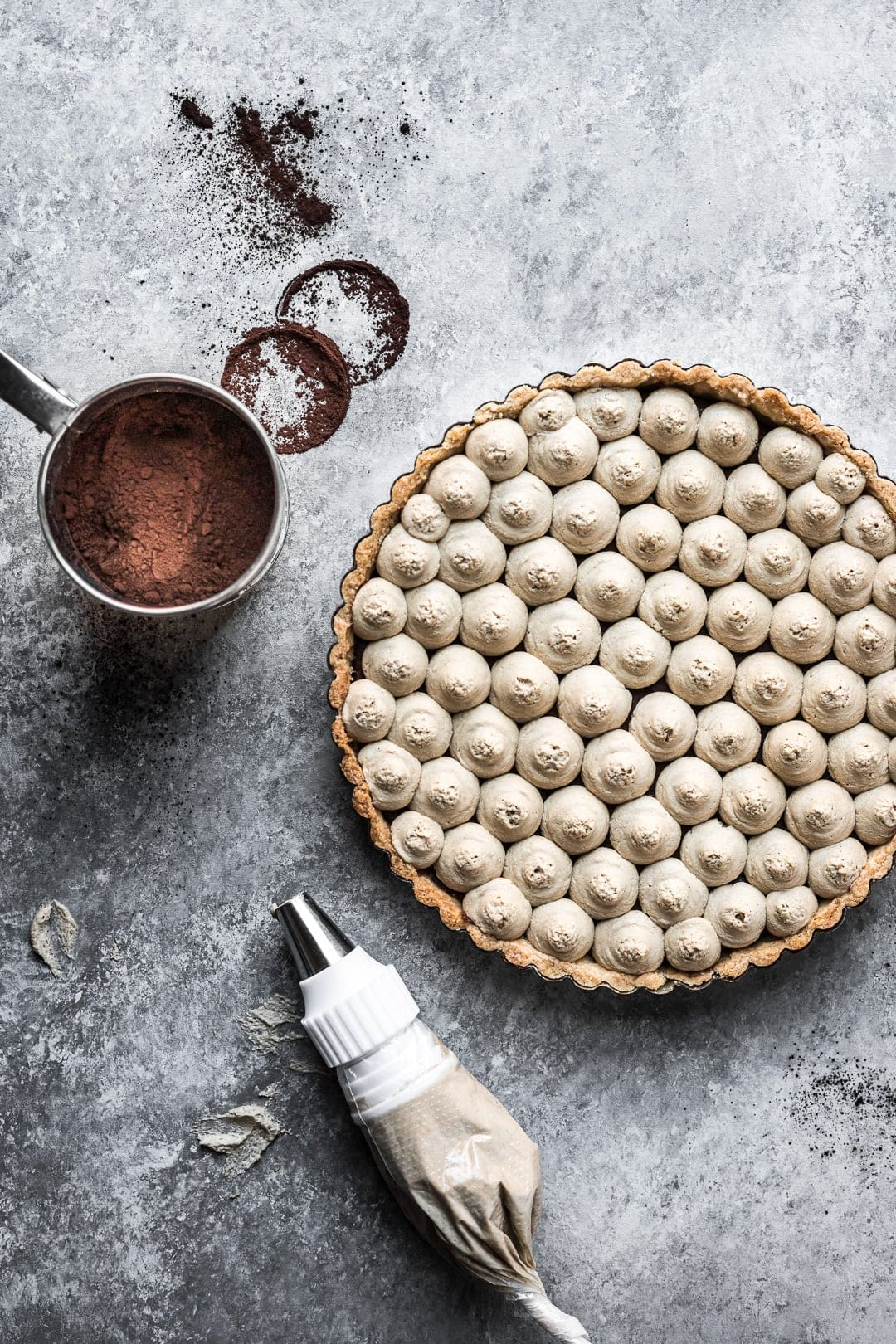 Chocolate coffee mascarpone tart on a grey background with cocoa powder and piping bag nearby