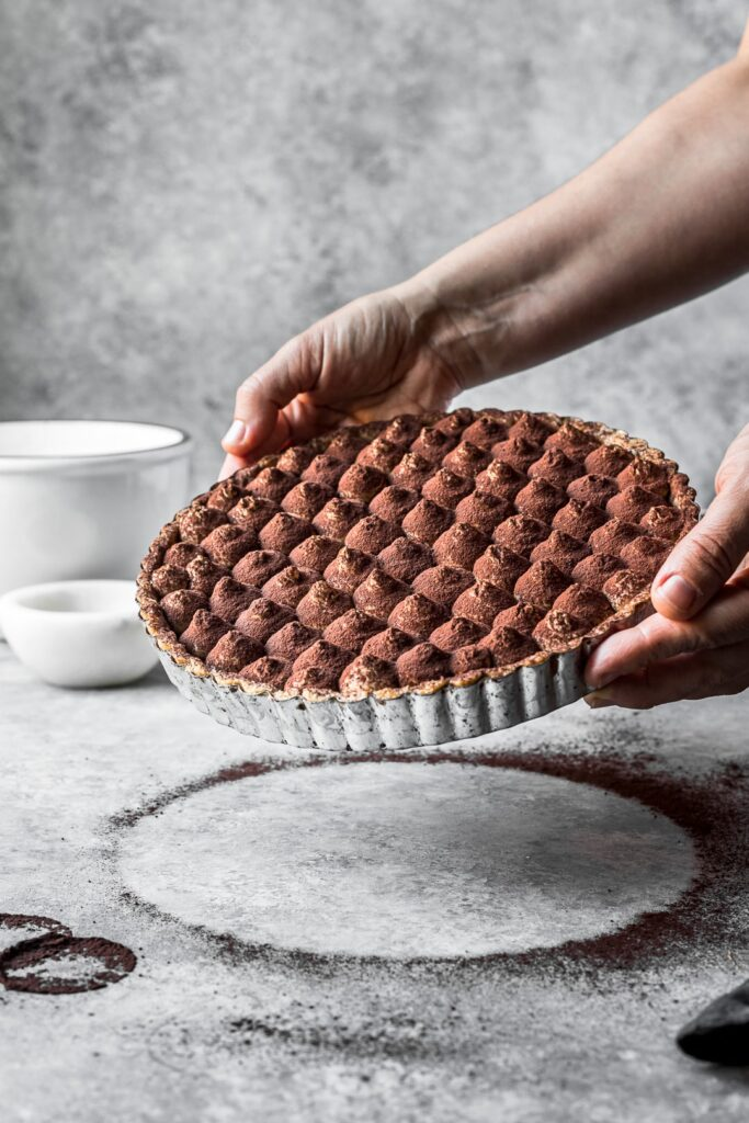 Hands holding a chocolate coffee mascarpone tart for display against a grey background