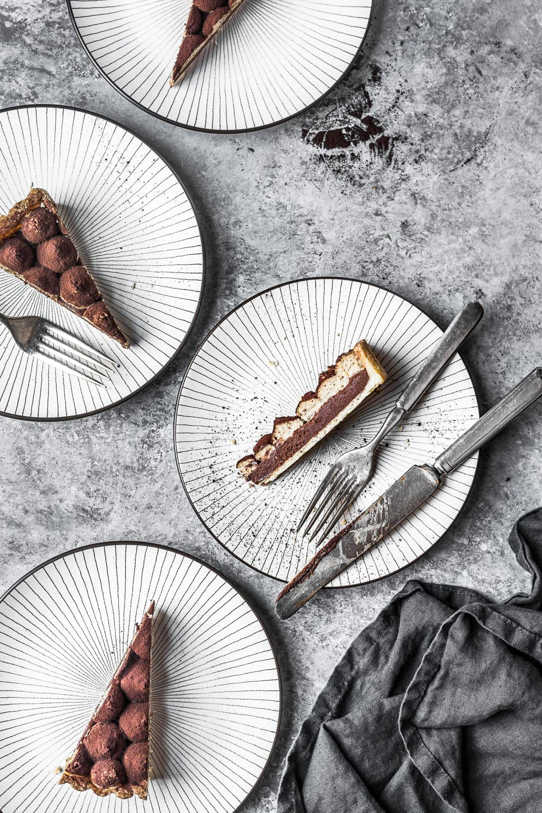 Sliced chocolate coffee mascarpone tart on plates with grey background behind