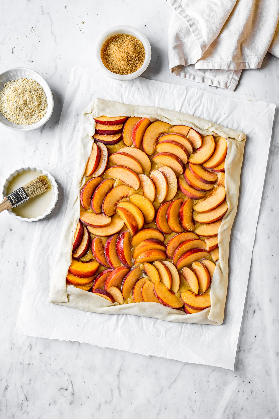 Unbaked peach galette on a white marble background