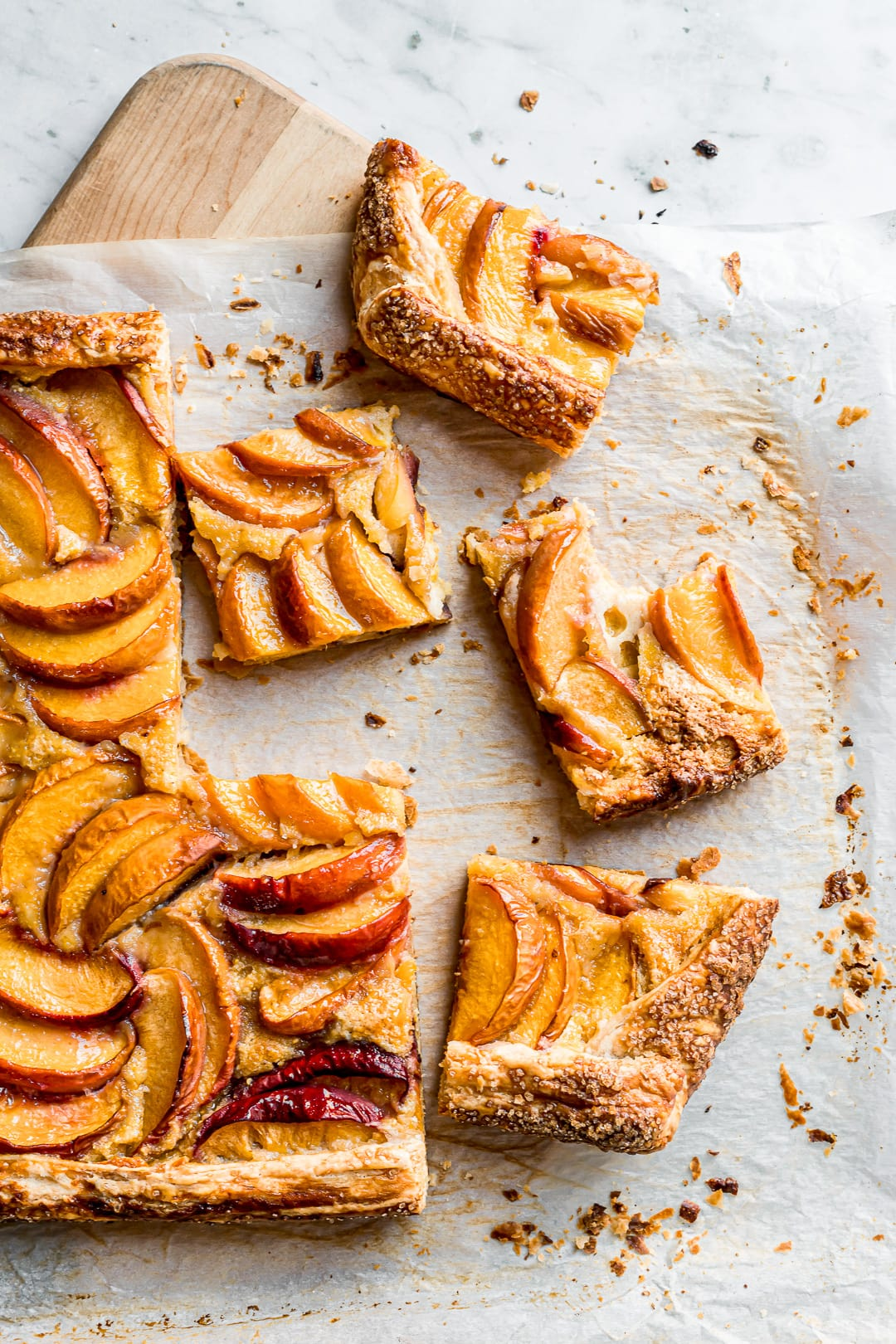 Peach galette slices on parchment paper and a cutting board