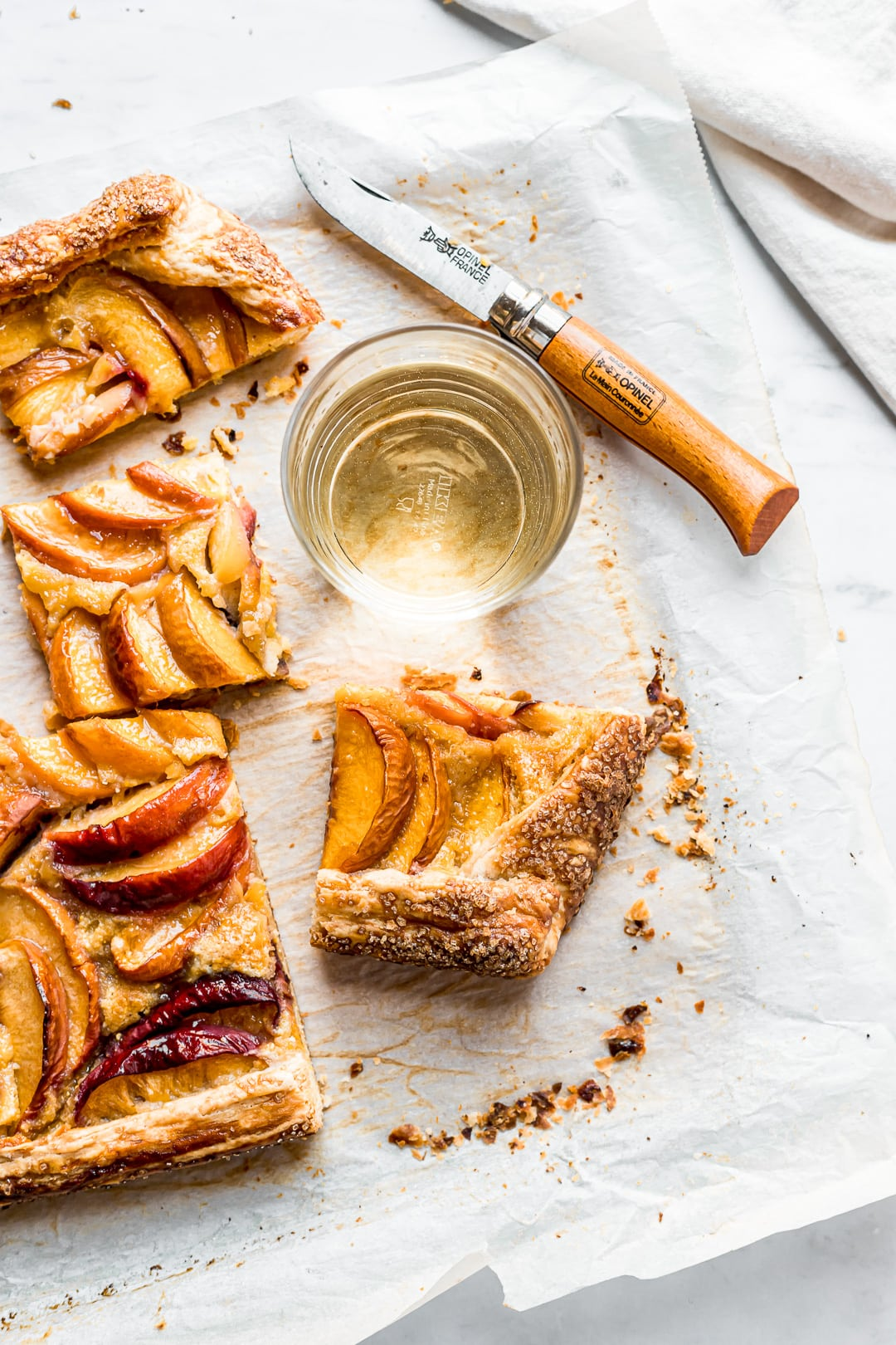 Peach galette slices on parchment paper and a cutting board with white wine and knife nearby