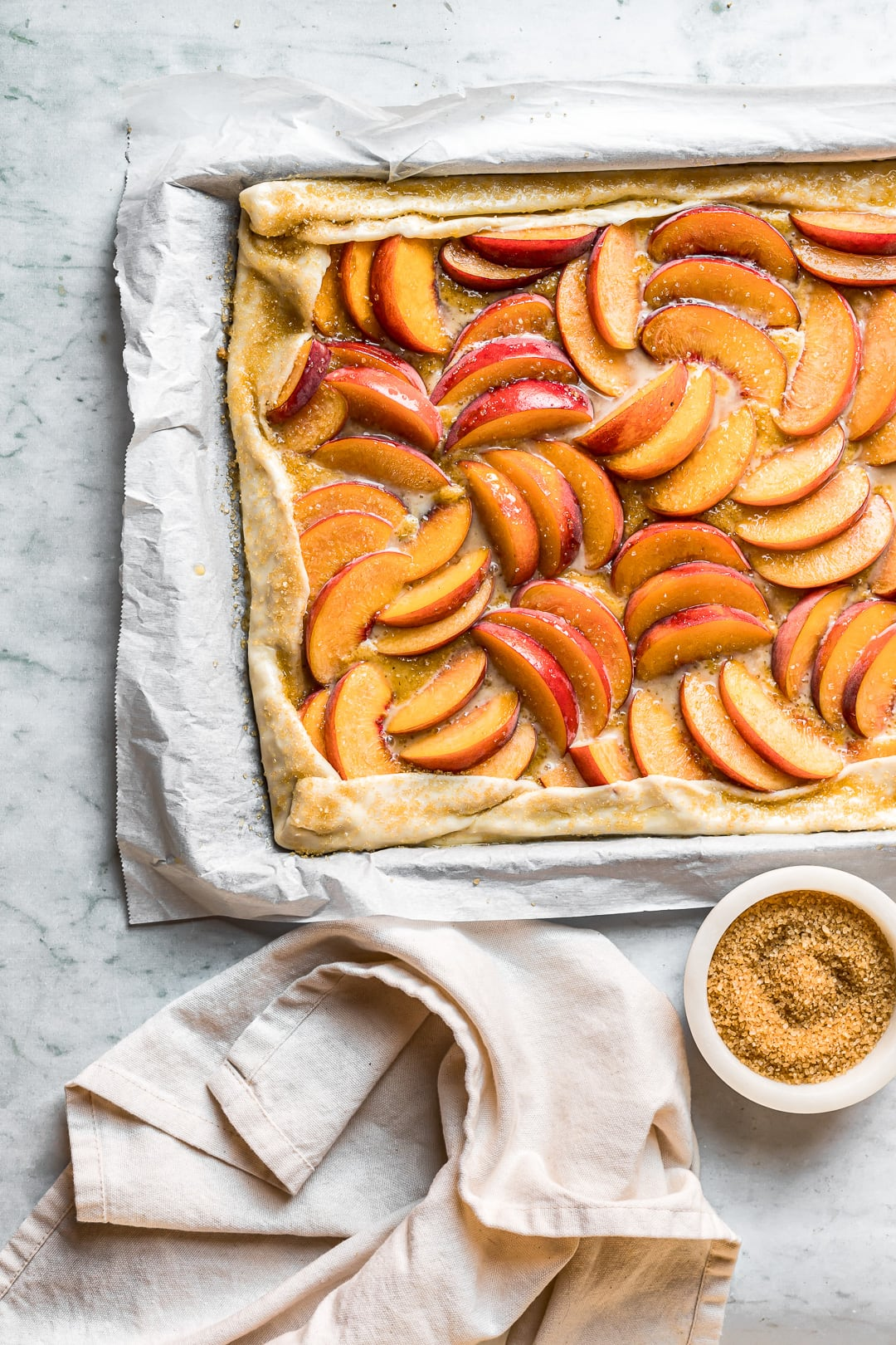 Closeup of unbaked peach galette on parchment and a white marble background